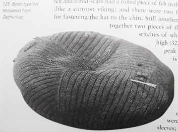 A three quarters top view of the beret style hat with the embedded twig to the front right and the damaged section to the back left.