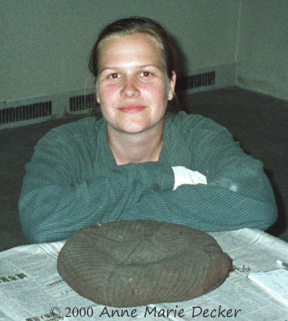 The photo shows Anne Marie Decker with her arms crossed (one white glove showing) and resting on a table covered with Chinese newsprint on which the Tarim hat is placed, right side up with the embedded stick in the left quarter nearest Anne and the damaged section to the right from the viewer's perspective.